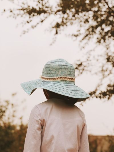 Rear View Of Girl In Hat Standing Against Sky