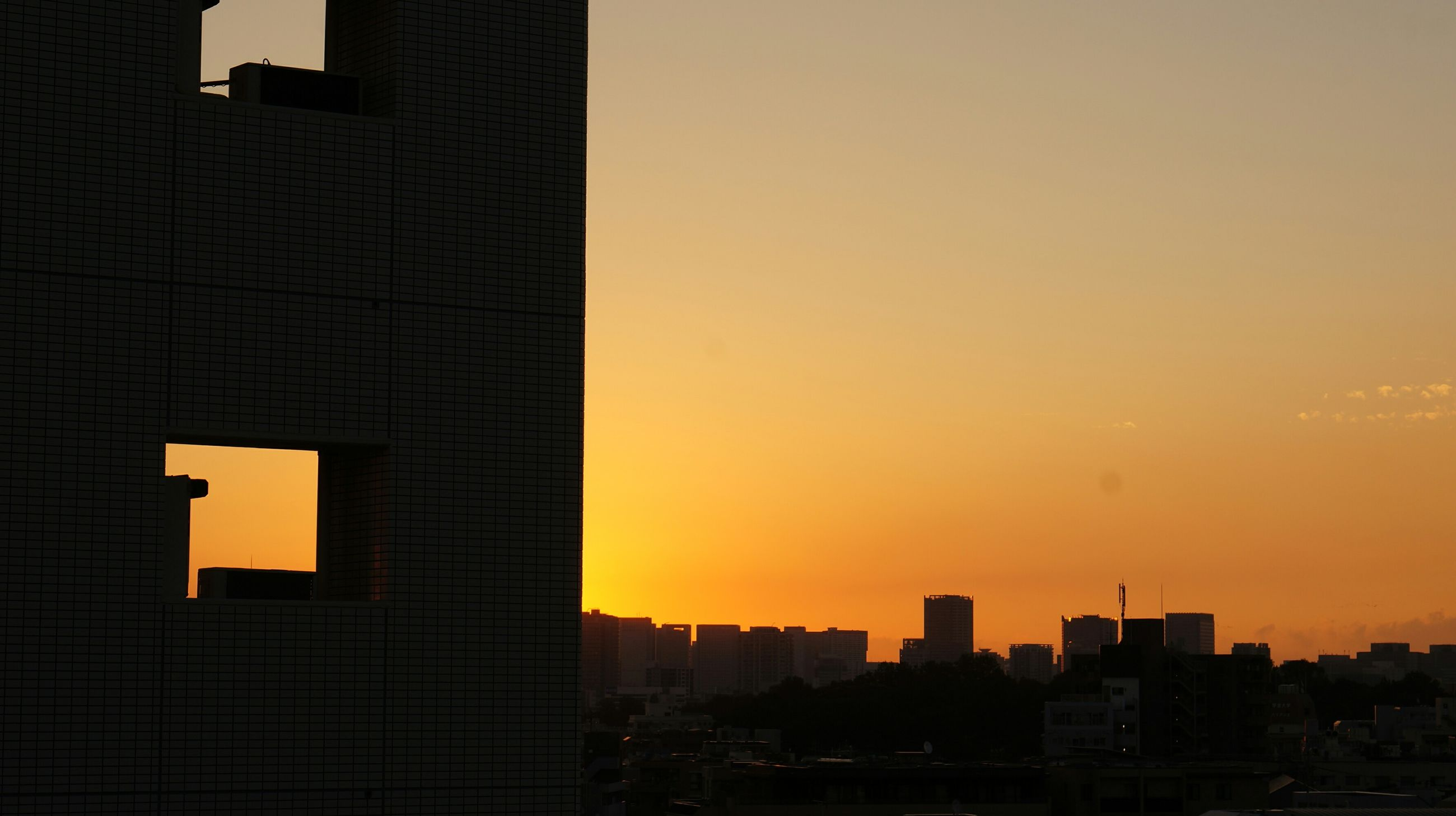 building exterior, architecture, sunset, built structure, city, skyscraper, orange color, modern, clear sky, office building, tower, tall - high, copy space, cityscape, building, silhouette, city life, urban skyline, sky, outdoors