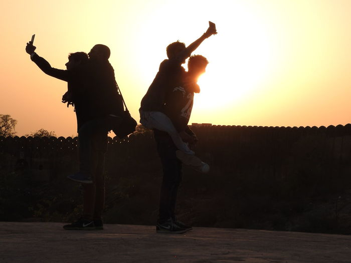 Silhouette friends taking selfie against clear sky during sunset