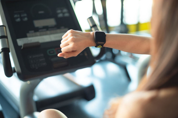 Close-up of woman wearing smart watch in gym