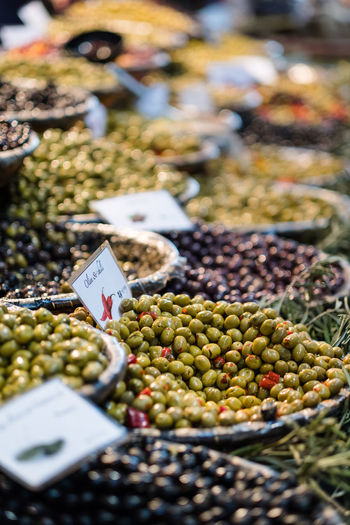 mixed olives on display in market EyeEmNewHere Green Abundance Choice Consumerism Food Food And Drink For Sale Freshness Fruit Green Olive Healthy Eating High Angle View Large Group Of Objects Market Market Stall No People Olive Price Tag Retail  Retail Display Sale Selective Focus Variation Wellbeing