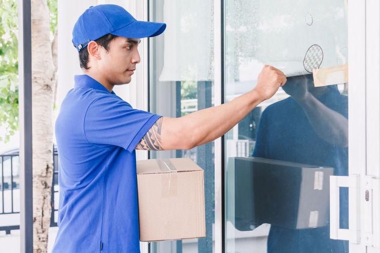 Salesman knocking door while standing with cardboard box