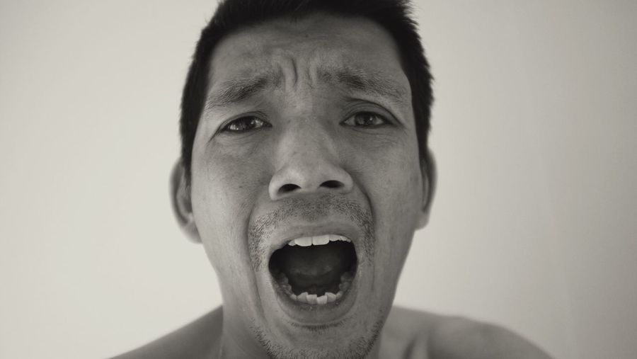 Close-up portrait of frustrated man shouting against wall