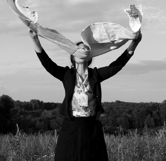 Full length of woman standing on field against sky with raised towel in her hands