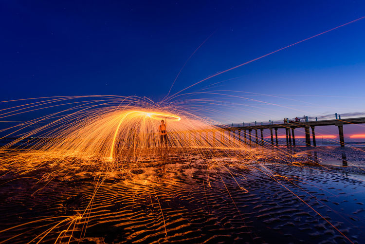 playing the fire in twilight time Water Sea Spraying Motion Clear Sky Long Exposure Sky Light Trail Light Painting Wire Wool Spinning Fireball