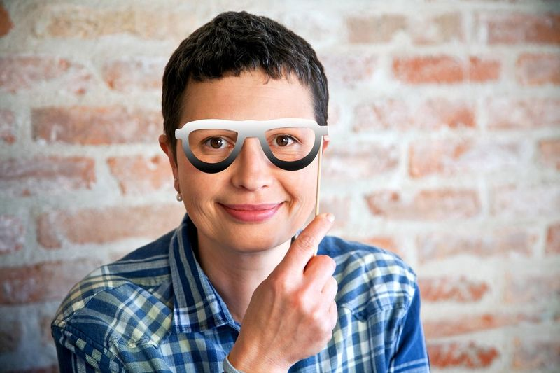 Portrait Of Smiling Woman Holding Eyeglasses Prop Against Brick Wall