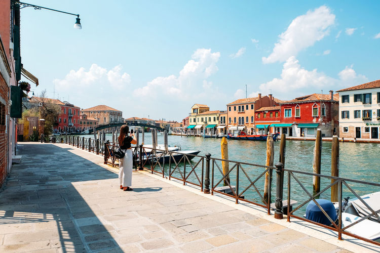 girl taking photo in the distant Architecture Building Exterior Built Structure Building Day Outdoors Venice Italy Burano Murano City Summer Sky Water Cloud - Sky Nature Transportation Real People Residential District Railing Nautical Vessel People Sunlight Mode Of Transportation Canal