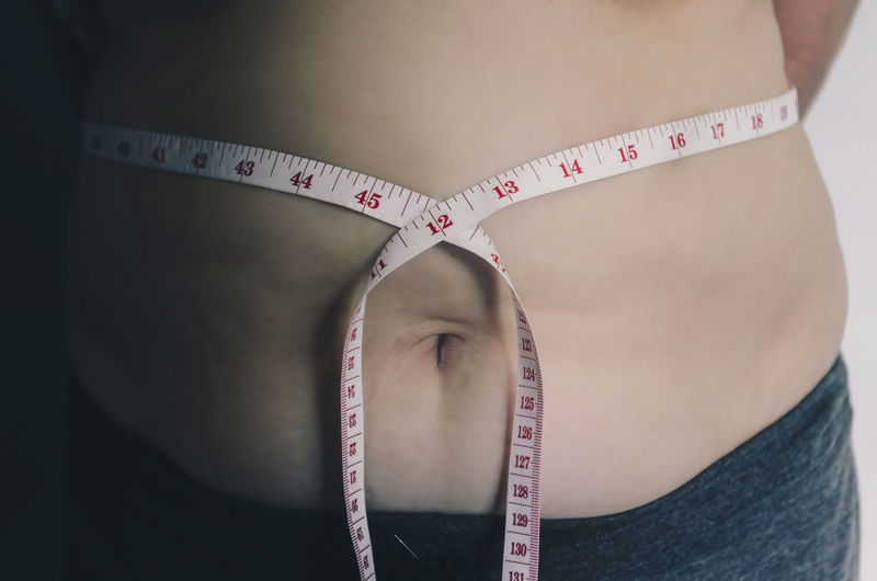 Close-up of human body and fat body, Fat body part of paunch or belly, Overweight of people or excess weight with measuring tape. Body & Fitness Diet Heavy Measuring Measuring Tape Obesity Overweighted Stomach Belly Body Care Body Part Bodyart Dieting Fat Father Human Body Part Measurement Measurements Overweight People person Tape Tape Measure Weight Weights
