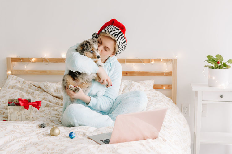 Woman in santa hat kissing cute puppy dog pet. woman calling family friends on video call online
