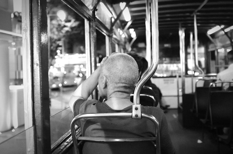 Rear view of mature man sitting in train
