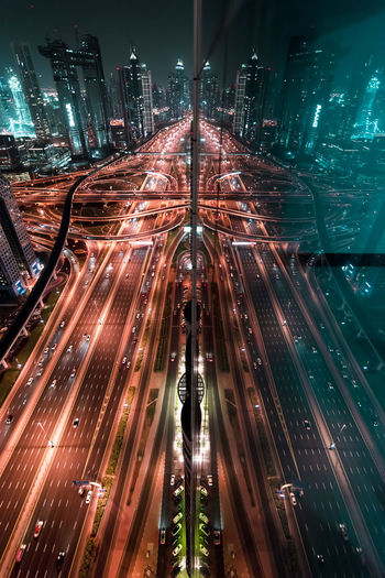 High angle view of light trails on road against buildings at night