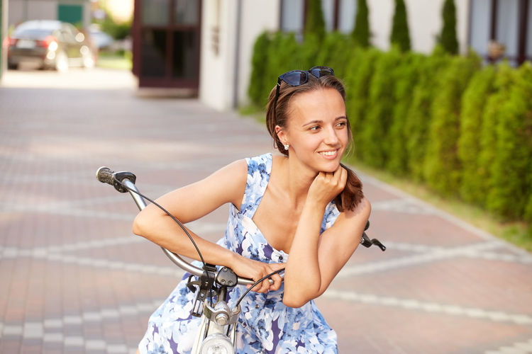 Cute woman cyclist in blue dress standing with bicycle in city smiling
