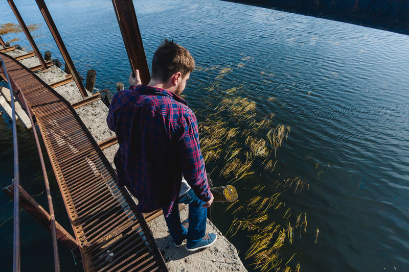 High angle view of man standing on retaining wall by river