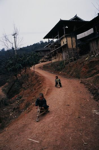 People riding motorcycle on road by building against sky