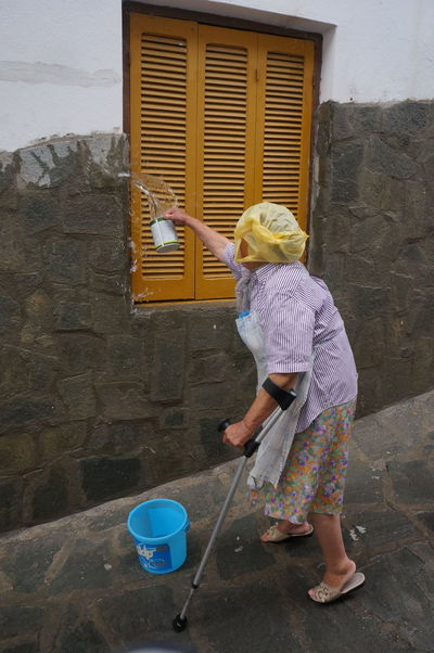 old women cooling the house Architecture Blond Hair Building Exterior Built Structure Casual Clothing Childhood Chores Cleaning Cleaning Equipment Day Full Length Holding Housework Lifestyles One Person Outdoors People Real People Standing Washing Water Working Young Adult Paint The Town Yellow This Is Aging