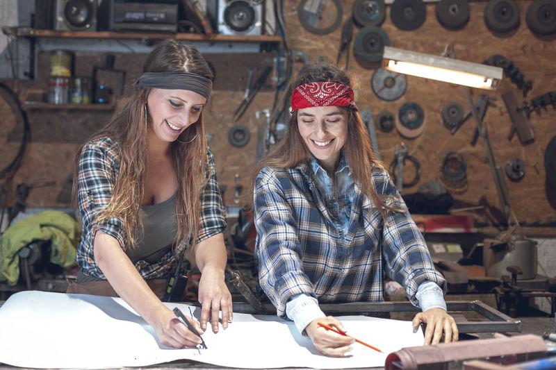 Smiling women drawing blueprint in workshop