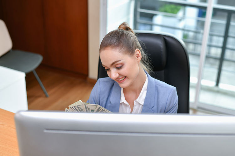 Portrait Of Smiling Businesswoman Holding Paper Currency While Sitting At Desk In Office