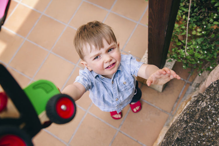 High angle view of cute boy crying while standing on tiled floor