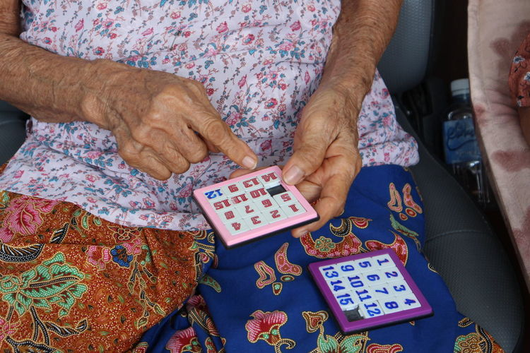 Midsection Of Senior Woman Playing Puzzle While Sitting On Chair
