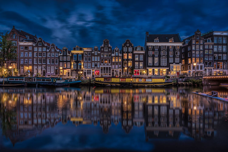 Amsterdam Architecture Blue Building Exterior Building Story Built Structure Canal City City Life Cloud Cloud - Sky Dusk Illuminated In Front Of Nautical Vessel Reflection Reflection Lake Residential Building Residential District Residential Structure Singel Sky Travel Travel Destinations Waterfront
