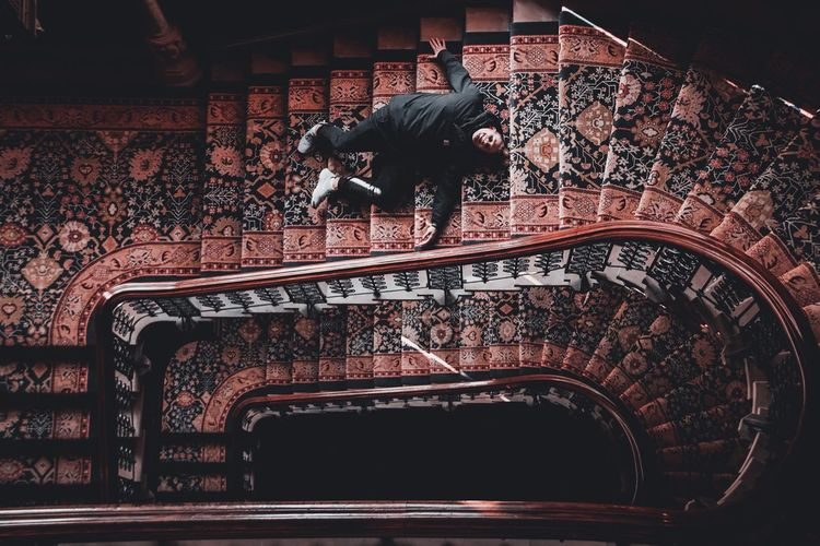 High Angle View Of Man Lying On Staircases