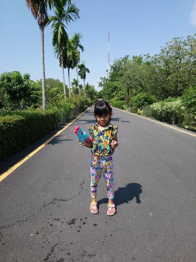 Girl with umbrella on road against sky