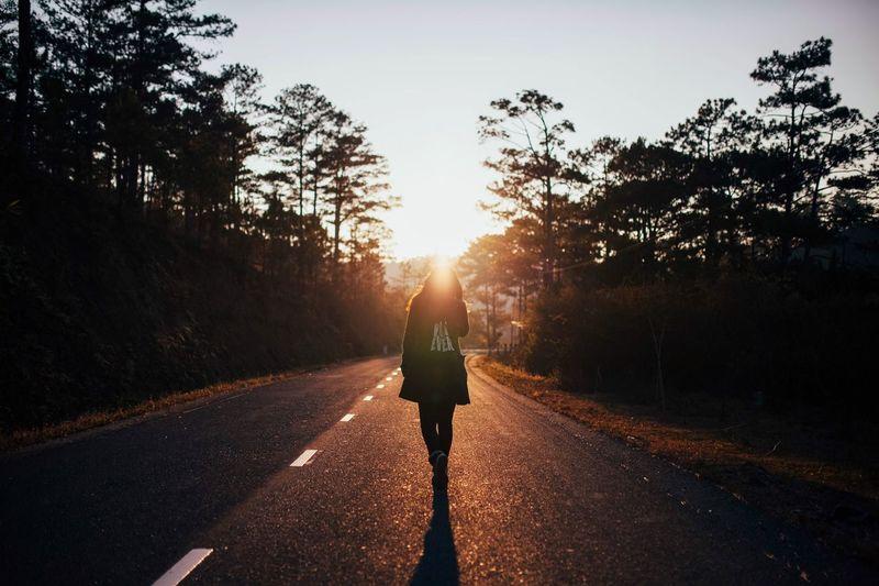 Man walking on road at sunset