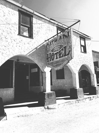 """Oatman Hotel"" The famous Oatman Hotel in the historic mining town of Oatman, Arizona was established in 1902. The eight room hotel did a brisk business to area miners, especially after two miners struck a rich vein that would end up being a 10 million dollar gold find in 1915. On March 29, 1939 Clark Gable and Carole Lombard spent their wedding night there after having been married in Kingman, Arizona. Travel Destinations Black And White Photography Blackandwhite Photography Black And White Blackandwhite Arizona Historic Hotel Historic Site Historic Building Historic Architecture Built Structure Building Exterior No People Building"