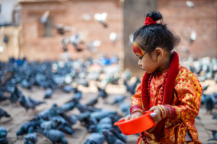 Girl wearing traditional clothing feeding crows