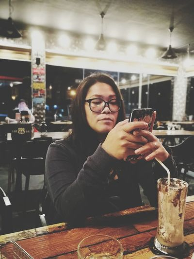 In My Own World Black Glasses Filipino Filipina Woman Cafe Cafe Time Frappuccino Wireless Technology Eyeglasses  Technology Cellphone Text Messaging Mobile Phone Using Phone Smart Phone Beverage