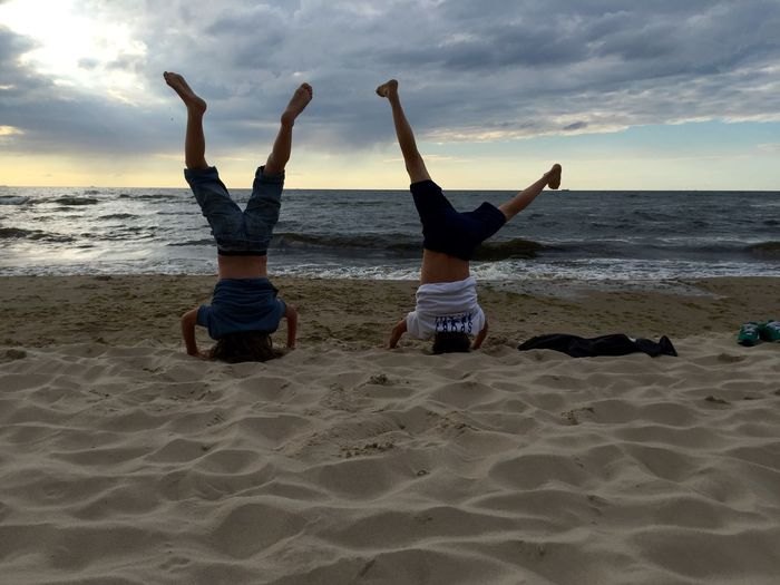 Rear View Of Boys Practicing Headstand On Sand At Beach During Sunset