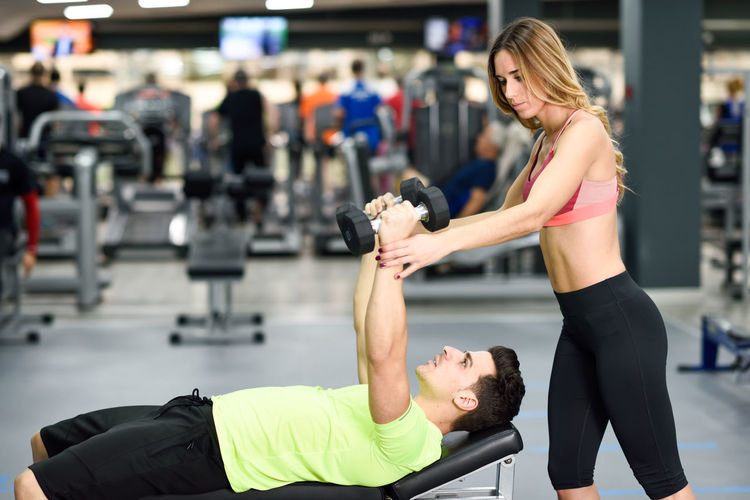 Trainer Assisting Man Exercising In Gym