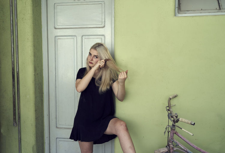 Full length of young woman against door