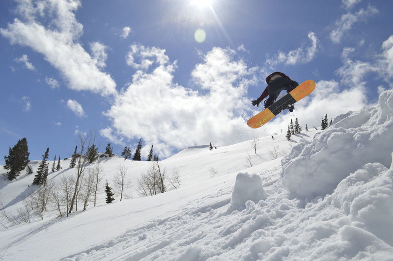 Low angle view of person snowboarding on snowcapped mountain against sky