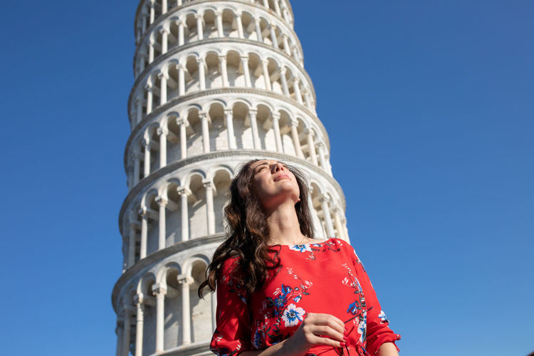Woman standing against leaning tower of pisa in italy