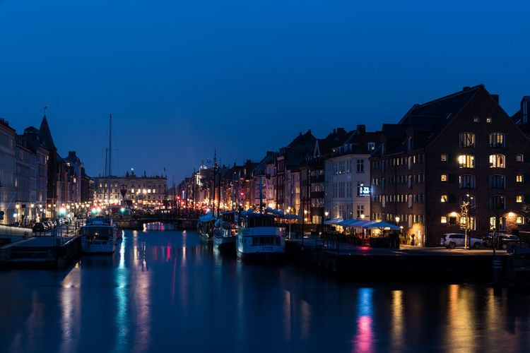 Sailboats moored on illuminated canal by buildings against sky at dusk