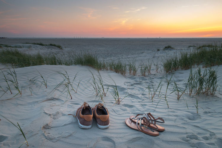 High angle view of shoes on beach against sky during sunset
