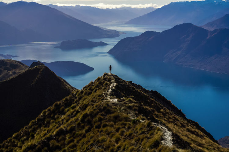 A man in awe with the view at the top of the roy's peak 1578m from the sea level Mountain Hiking Landscape Mountain Range Mountain Peak Scenics Lake Nature Travel Destinations Beauty In Nature New Zealand Tranquility Travel Photography First Eyeem Photo Lost In The Landscape