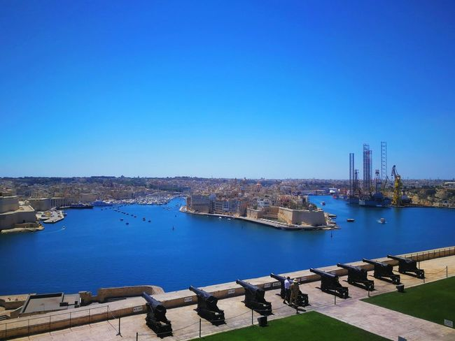 Blue Architecture Sky Outdoors City Day Cityscape Sunny Malta Scenic Cannon Gun Travel Destinations Built Structure Sea Deep Blue Fortification Stronghold Valletta,Malta Protected Area High Angle View