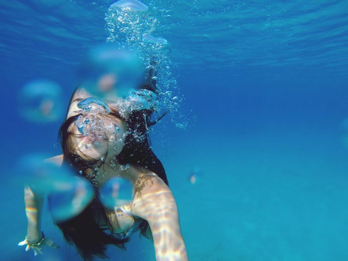 Close-up of young woman swimming in sea