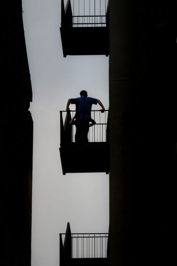 Low angle view of silhouette friends standing in balcony against sky