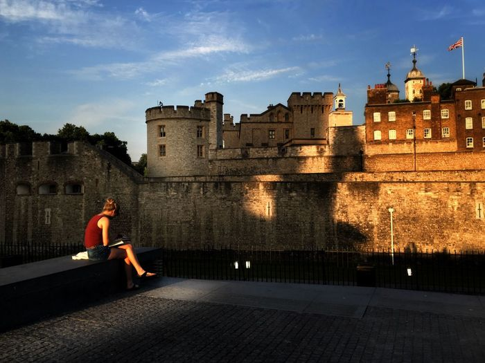 London Tower at dusk Architecture Building Exterior Built Structure Full Length One Person Castle Sky History Outdoors Day Urban Impressions Cloud - Sky Sunlight Lifestyles Reading Alone London Lonely High Contrast Ray Of Light Evening Real People Women One Woman Only City EyeEm LOST IN London Your Ticket To Europe Postcode Postcards
