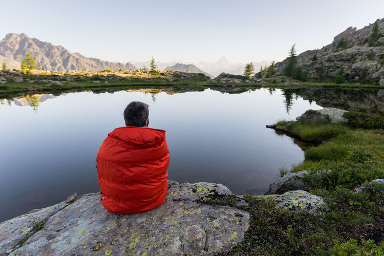 Rear view of man looking at lake against mountain