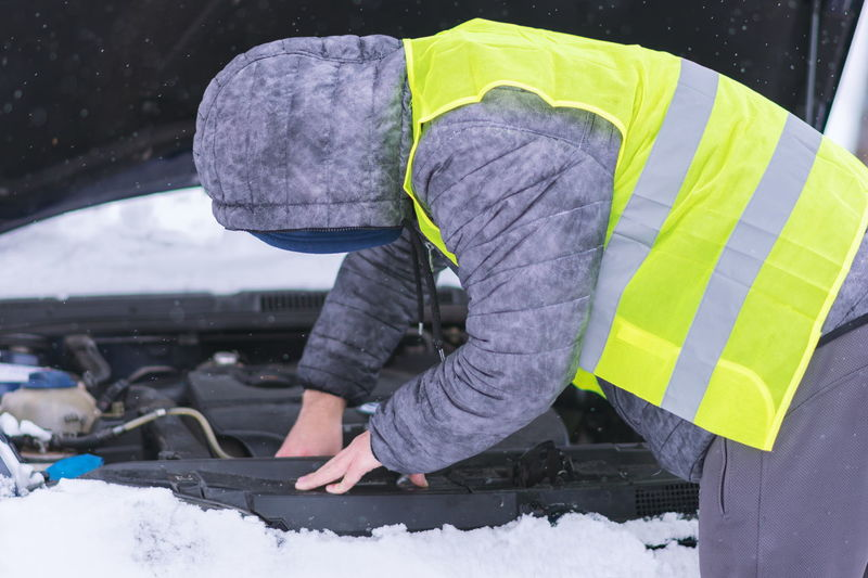 Side view of man repairing car