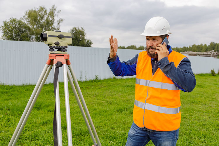 Man working with umbrella standing on field