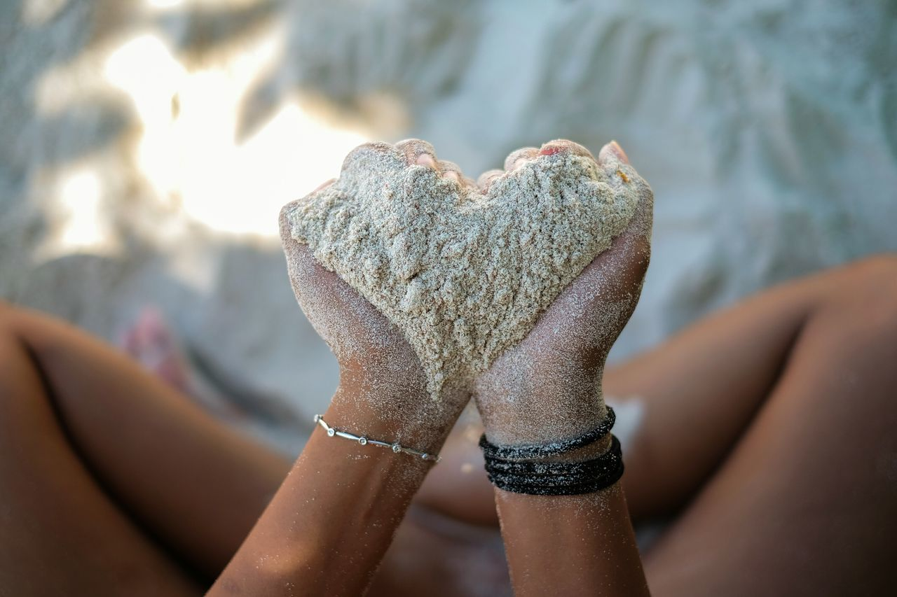 Midsection Of Woman Holding Sand In Heart Shape At Beach