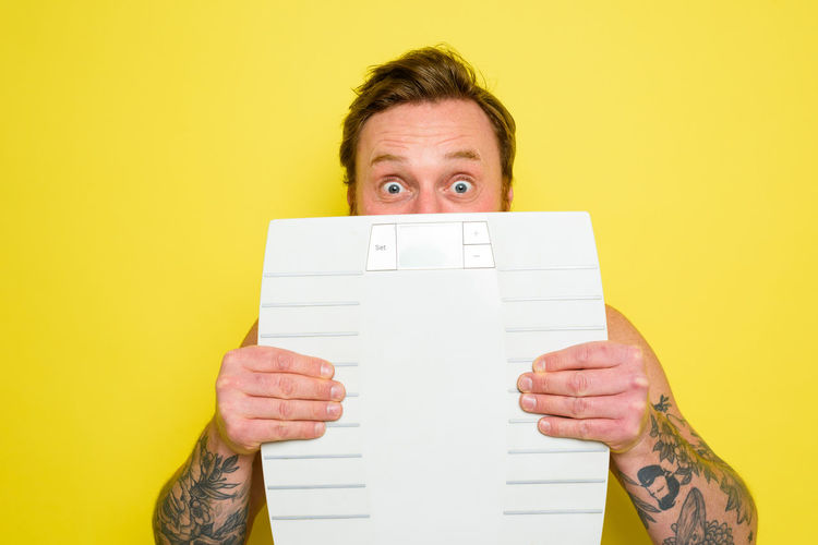 Portrait of man holding paper against yellow background