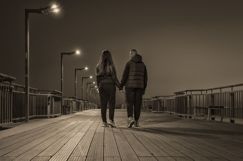 Rear view of couple walking on pier against sky