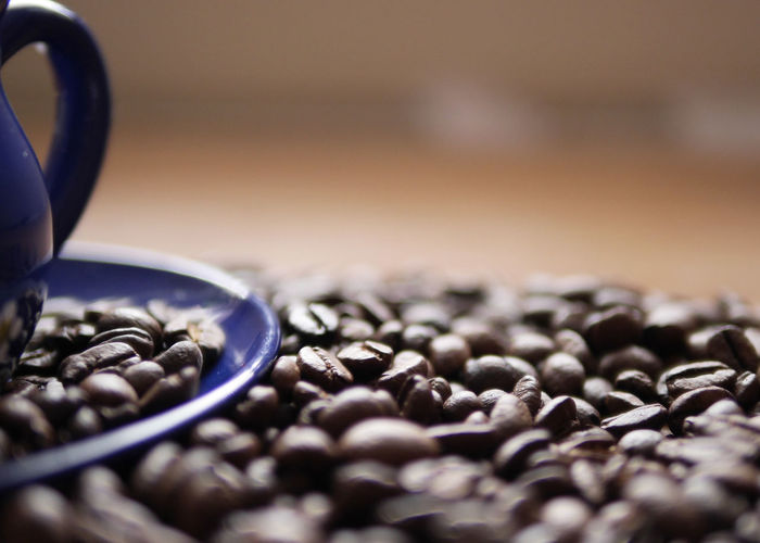 Close-up of coffee beans with cup and saucer on table