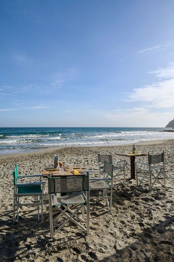 beach bar Beach Bar Empty Beach Tranquility Tables And Chairs Tablesetting On The Beach On The Sand Seascape Travel Destinations Silence Sea Beach Horizon Over Water Water Chair Sky Sand No People Day Blue Nature Outdoors Clear Sky